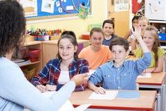Domanda di risposta dell'allievo elementare maschio nella classe Immagini Stock