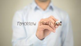 Domani ora inizia, scrittura dell'uomo sullo schermo trasparente Immagini Stock