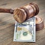 Domare eller auktionsförrättare auktionsklubba och pengarbunt på träbakgrund Arkivfoto