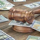 Domare eller auktionsförrättare auktionsklubba och pengarbunt på träbakgrund Arkivfoton