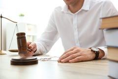 Domare med auktionsklubban p? tabellen i r?ttssal Lag- och r?ttvisabegrepp royaltyfri foto