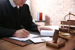 Domare som arbetar med legitimationshandlingar och auktionsklubban p? tabellen, closeup Lag och r?ttvisa royaltyfri foto