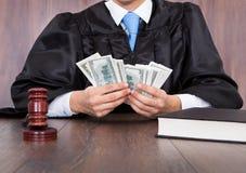Domare som räknar pengar Arkivbilder