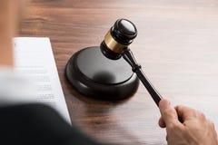 Domare som slår auktionsklubban på skrivbordet Arkivfoton