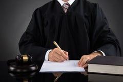 Domare Writing On Paper i rättssal arkivbild