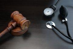 Domareauktionsklubba och medicinsk utrustning på svart träbakgrund Arkivfoton