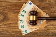 Domareauktionsklubba- och pengarbunt på trätabellen Arkivfoto