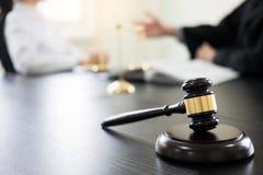 Domareauktionsklubban med advokater råder lagligt på advokatbyrån i bakgrund royaltyfri bild