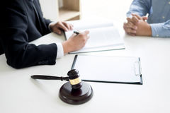 Domareauktionsklubban med advokater råder lagligt på advokatbyrån i bakgrund Arkivfoton