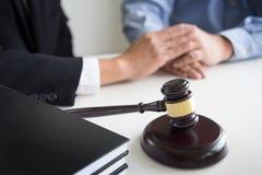 Domareauktionsklubban med advokater råder lagligt på advokatbyrån i bakgrund Arkivbilder