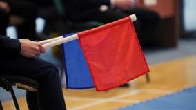 Domaren av kampsporter rymmer den röda och blåa flaggan lager videofilmer