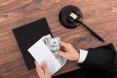 DomareRemoving Money From kuvert Royaltyfria Bilder
