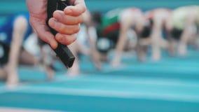 Domares hand med startpistolen på suddig bakgrund av idrottsman nen stock video
