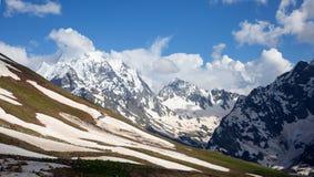 Dombai山多雪的山峰在春天末期的 免版税库存照片