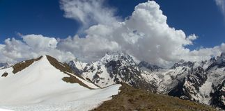 Dombai山多雪的山峰在春天末期的 库存图片