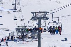 Dombai,俄罗斯12月7日2017年:滑雪者和挡雪板举到在冬天雪山的滑雪胜地上流在 免版税库存图片