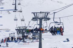 Dombai, Russia-December 7, 2017: skiers and snowboarders lift to the Ski Resort high in the winter snow mountains at. Chair cable car royalty free stock image