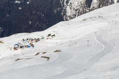 Skiing pistes leading to a small village in the mountains stock images