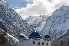 Beautiful mosque on the background of the snow-capped Caucasus Mountains. DOMBAY, RUSSIA, FEBRUARY 28, 2018: Beautiful mosque on the background of the snow stock photography