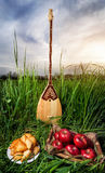 Dombra and Kazakh food. Dombra Kazakh instrument, apples and baursak dish on the grass at sunset sky Stock Photo