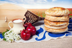 Dombra and Kazakh food. Dombra Kazakh instrument, apples, milk and bread lepeshka on the table at poppy flower field background Royalty Free Stock Photo