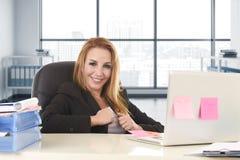 Domderande affärskvinna med blont hår som ler säker benägenhet på kontorsstol som arbetar på bärbar datordatoren Royaltyfri Foto