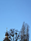 Dome of the Christian church can see ot the trees against the bl. Golden Cross Church and the tops of trees on a blue background. Concept: Easter, religious Royalty Free Stock Image