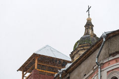 Dome and a cross of an old church. Moscow, Russia, February 4, 2013. Heavy snowstorm. Ilyinka street. Dome and a cross of an old church against the snowy sky stock images
