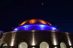 A dome with the moon. A dome with the moon in the evening with yellow color haughtiness and blue royalty free stock image