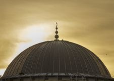 Dome of a mosque under construction visited by a bird at sunset under overcast sky.. The construction of a concrete dome requires a formwork which itself could royalty free stock photography
