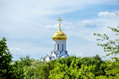 The dome of the Orthodox Church. Surrounded by among the green trees stock photo