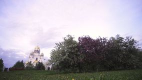 The dome of the Orthodox Church surrounded by flowering Apple trees and green meadow, religion concept. Stock footage. The dome of the Orthodox Church surrounded stock photos