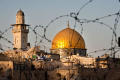 Dome of the Rock Through Barbed Wire. Jerusalem's Dome of the Rock and mosque minaret seen through barbed wire with Israeli flags flying in the foreground Royalty Free Stock Photo