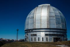 Dome of special astrophysical observatory on blue sky background at sunny day.  stock photos