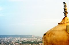 Dome & spires of an indian fort shot against a cityscape Royalty Free Stock Image