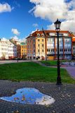 Dome Square in Riga in the autumn. Dome Square in Riga with reflection in a puddle with yellow leaves of a blue sky in autumn stock photography