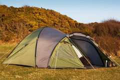Dome tent pitched in field. For wild camping in the great outdoors with front flap open showing interior stock photo