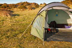 Dome tent pitched in wilderness. Dome tent pitched in field for wild camping in the great outdoors with front flap open showing interior and copy space on left royalty free stock images