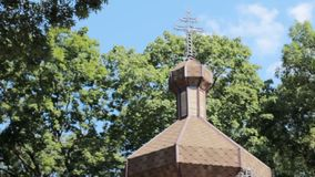 The domes of an ancient wooden Orthodox church. Cross at the top. Close up stock video