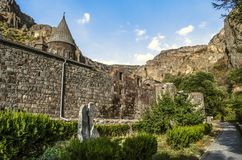 Domes of the church and the bell tower behind a stone wall with a park around the Geghard monastery against the backdrop of Gegham royalty free stock photos