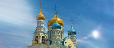 The domes of the Orthodox Church, amid blue skies, gleaming Golden domes. With the Sun Stock Images