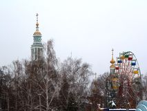 Domes of the Orthodox crosses and Ferris wheel. Royalty Free Stock Image