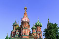 Domes of St. Basil`s Cathedral against green trees and blue sky on a sunny summer morning Stock Images