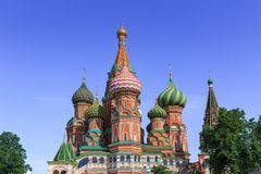 Domes of St. Basil`s Cathedral against green trees and blue sky on a sunny summer morning Royalty Free Stock Images