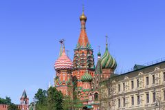 Domes of St. Basil`s Cathedral on Red square against blue sky Stock Photos