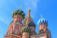 Domes of St. Basil`s Cathedral on Red square on a blue sky background Stock Photos