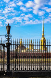 The domes of St. Peter and Paul cathedral seen through the fence of Museum of Artillery. Royalty Free Stock Photo