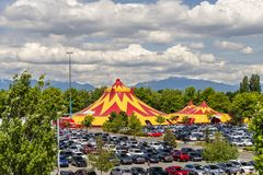 Domes of the tent of a traveling circus in the city, green trees stock photography