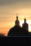 Domes. View of the domes of Grand Ducal Burial Vault on territory of Peter and Paul Fortress in the background of the cloudy winter sky, backlit. Saint Royalty Free Stock Photography