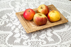 Domestic apples in a wicker basket on embroidered tablecloth Royalty Free Stock Images